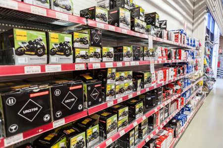 car retailer: LAPPEENRANTA, FINLAND - CIRCA FEB, 2017: A lot of new motorcycle batteries are on the racks of car accessories shop. The Motonet is a large chain retailer of auto and motorgoods in Finland Editorial