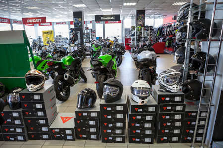 motor bike: ST. PETERSBURG, RUSSIA - CIRCA FEB, 2017: Motorcycle helmets and outfit of Dainese are in dealer showroom with motorbikes. Official dealership of Kawasaki and Ducati brands is in city Editorial