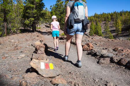 Signposted with colors of Spanish flags hiking trail to Lunar landscape (Paisaje Lunar). Woman and child walking stony and volcanic way, Tenerife, Canary islands, Spain Stock Photo