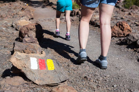 Signposted with Spanish flags colors hiking route to Lunar landscape (Paisaje Lunar). Woman and child legs passing stony trail, Tenerife, Canary islands, Spain Stock Photo
