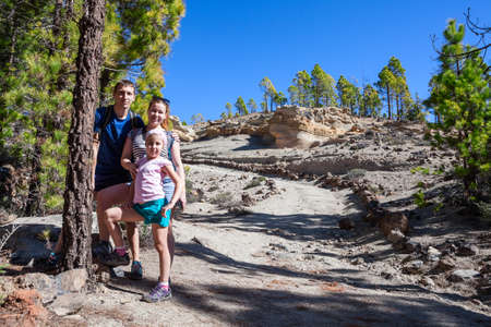 Three people family hiking in Teno national park. Walkway to Lunar Landscape. Tenerife, Canary, Spain, Europe