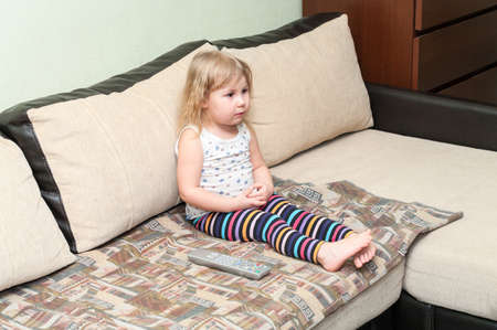Small Caucasian girl sitting on the sofa and watching tv with fixedly look, remote control is near photo