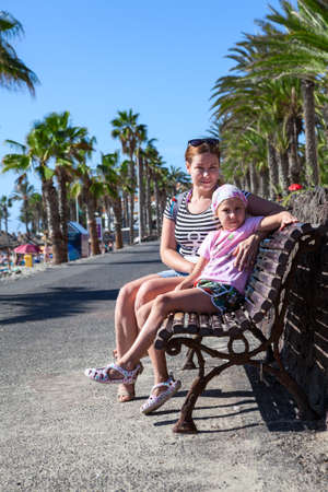 Mother and her daughter sitting on the bench in palm tree alley. Tenerife, Canary photo