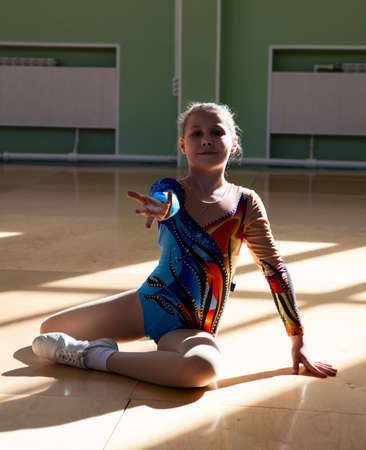 Portrait of an eight years old girl gymnast on the gym floor in the starting position before the performance photo