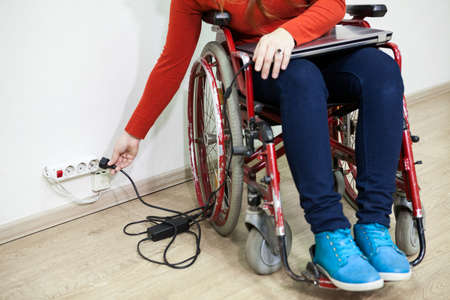 Caucasian woman hand stretching to power socket in wall. Disabled woman in wheelchair