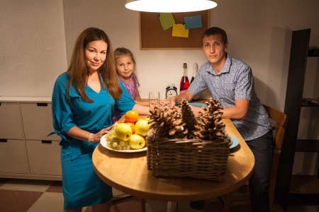 Portrait of three people family sitting at the table and celebrating festive occasion together photo