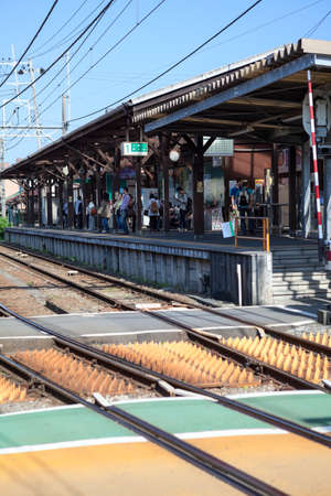 electric line: KAMAKURA, JAPAN — CIRCA APR, 2013: The Hase Station platform with waiting people is on Enoshima Electric Railway line. Station of Kamakura city. The Kanagawa Prefecture