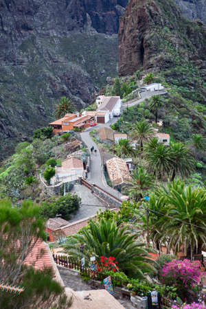 famous people: MASCA, TENERIFE, CANARY, SPAIN - CIRCA JAN, 2016: The only one paved street is in village of Masca. People walk on the road. Masca village is a famous tourist place with start of hiking trail through the gorge Editorial