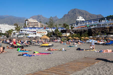 COSTA ADEJE, TENERIFE, SPAIN-CIRCA JAN, 2016: People lay on the sand and swim in the ocean at Torviskas beach. Torviscas beach is the beach of Fanabe with fine grey sand