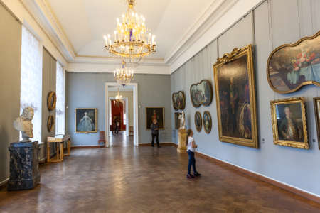 ST. PETERSBURG, RUSSIA - CIRCA APR, 2017: Young Caucasian girl stands near the art Portrait of Peter III by A. Antropov in the Russian State Museum in the Mikhailovsky Palace