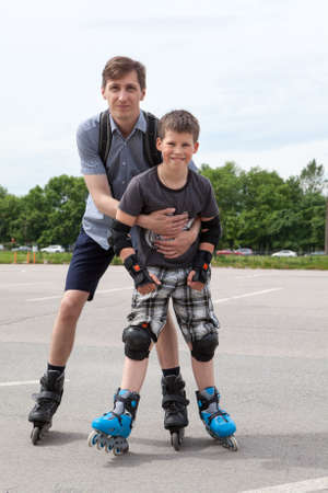 Father holding son while riding on roller-skates in city park Stock Photo