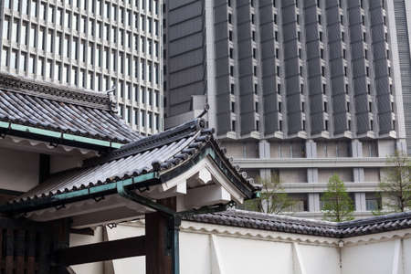 Ancient Japanese tile roofs against modern sky-scrapers in center of Tokyo city, Japan