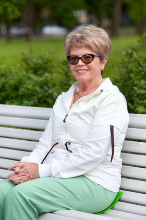 공원에서 산책하는 동안 유럽 여성 연금 수 탉 앉고 벤치에 달려있다