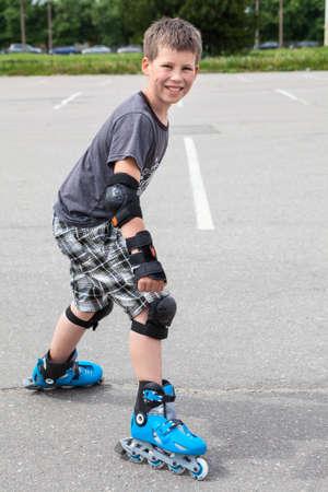 Sonriente joven listo para comenzar a montar en patines en el parque urbano