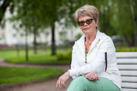 cogitations: Portrait of wise European senior woman. Sitting on the bench in park and looking at camera, copyspace
