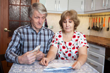 Surprised husband and wife looking at the bills with cash money in hands, domestic kitchen