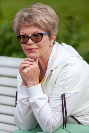 Portrait of thoughtful European senior woman outdoor, looking at camera Stock Photo
