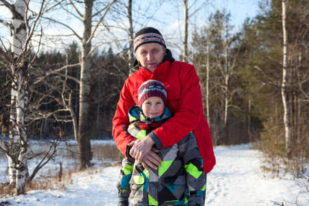 Portrait of hugging mature father and son in warm clothes in winter forest photo