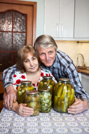 Smiling Caucasian aged couple sitting in domestic kitchen with glass cans with picklers photo