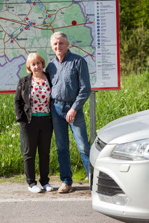 Full-length portrait of mature husband and wife standing behind the map while traveling by car photo