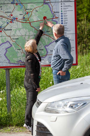 Mature husband and wife travel by car, looking at the map and pointing at the location place photo