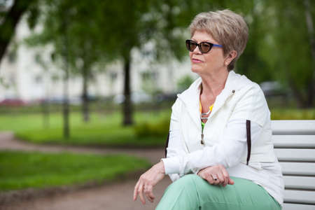 cogitations: Concentrated all thoughts European senior woman in eye glasses. Sitting on the bench in park and looking far away, copyspace