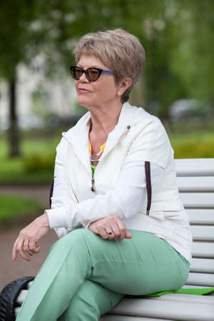 Concentrated European senior woman in eye glasses resting on the bench in park and looking far away