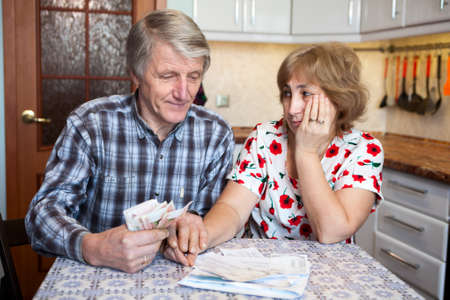Sad senior couple with cash money and papers with current account balance photo