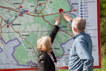 Mature husband and wife pointing on the map, finding location place photo