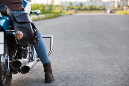 Motorcyclist standing on the highway ready to travel, copyspace with asphalt road