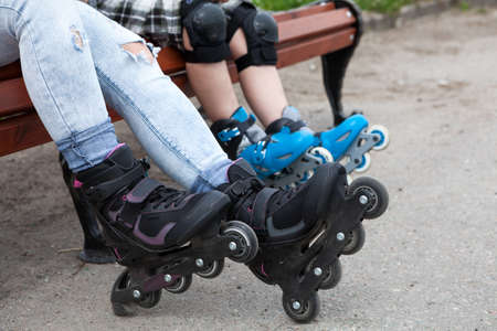 Close-up view at the in-line skates wearing on mother and children legs, people sitting on the bench photo
