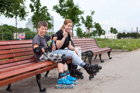 Young mom with ten years old son resting on the bench in urban park while rollerblading photo