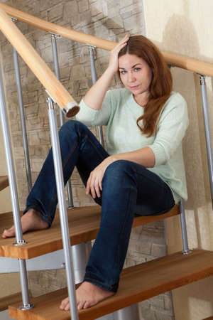 Young Caucasian woman sits on a wooden spiral staircase in her own home photo
