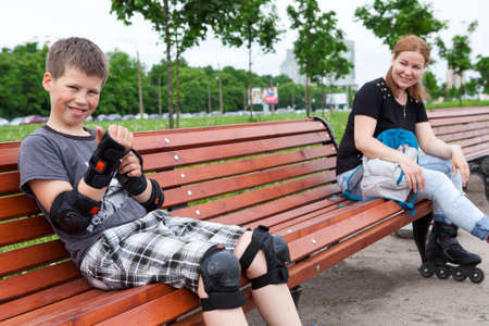 Mom and son resting on the beanch during roller skating together photo