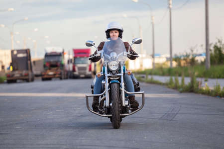 European woman riding chopper motorcycle on asphalt highway, front view photo