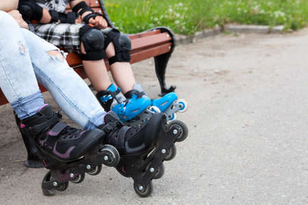 Close up view at the roller-skates wearing on female and boy legs, people sitting on the bench photo