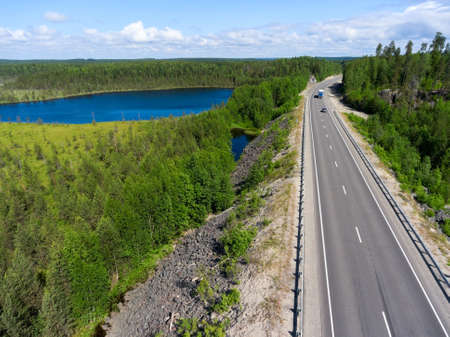 Aerial view at the country highway passing near forest lake in evergreen northern forests