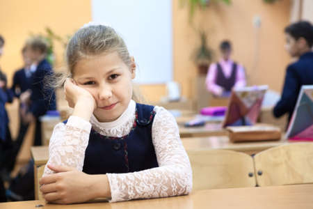 Young girl a pupil is in a bad temper on recess while other children playing on background