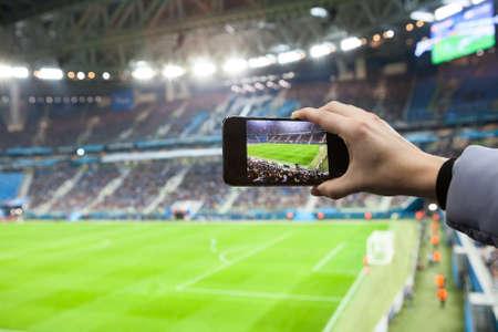 Ventilador, mão, com, smartphone, fotografar, footbal, jogo