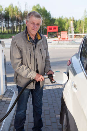 Senior European man filling the own car with gasoline in gas stations Stockfoto
