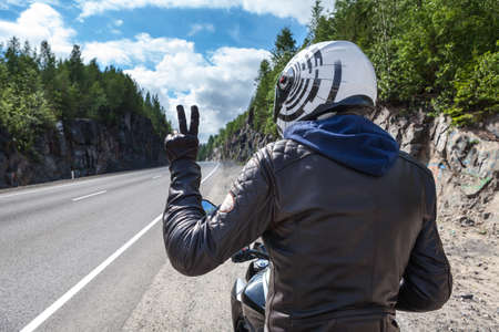 Motorcycle driver rear view at the asphalt road, sitting on motorbike and showing victory sign wit hand