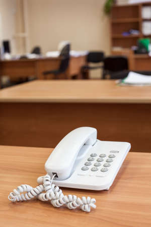 White fixed network telephone standing on office desk, empty room Stock Photo