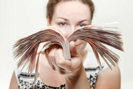 Close-up portrait of woman holding cash Russian roubles in hand, white background Stock Photo