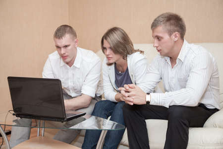 Two blond men and one woman sitting together at the glass table and using laptop