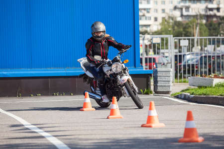 L-driver person drives slalom through the orange cones on motordrome on motorcycle