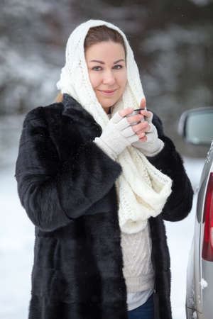 Attractive Caucasian woman warming with hot tea mug while standing with unbutton fur coat in white woolen scarf at winter season Stock Photo