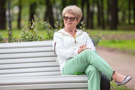 Smiling European elderly woman sitting on the edge of a white bench in the park Stock Photo