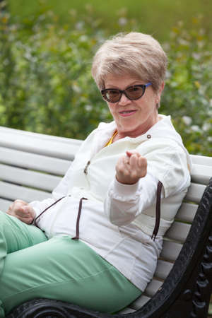 Aggressive elderly woman is threatened with a fist while sitting on a park bench Stock Photo