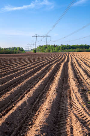 Freshly ploughed field with green rolling hills in the distance and power transmission lines Stock Photo