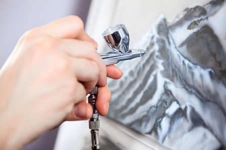 An aerograph unit or paint sprayer in human hand drawing on canvas, close up view Stock Photo